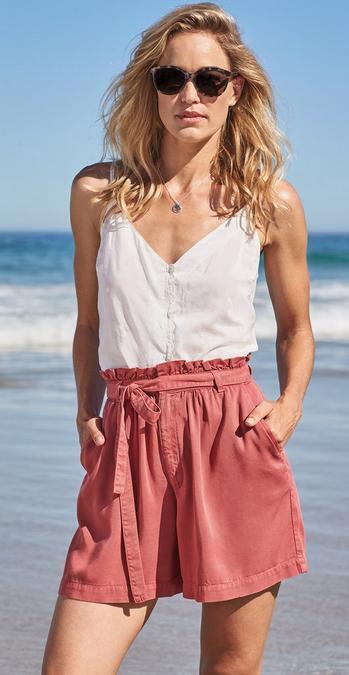 Female model stood on a beach wearing Tie Front Linen Blend Shorts in ash red and a white cami