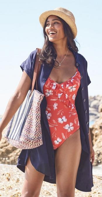 Model wearing a Bold Blooms Ruffle Eco Swimsuit with a open navy shirt dress and trilby.