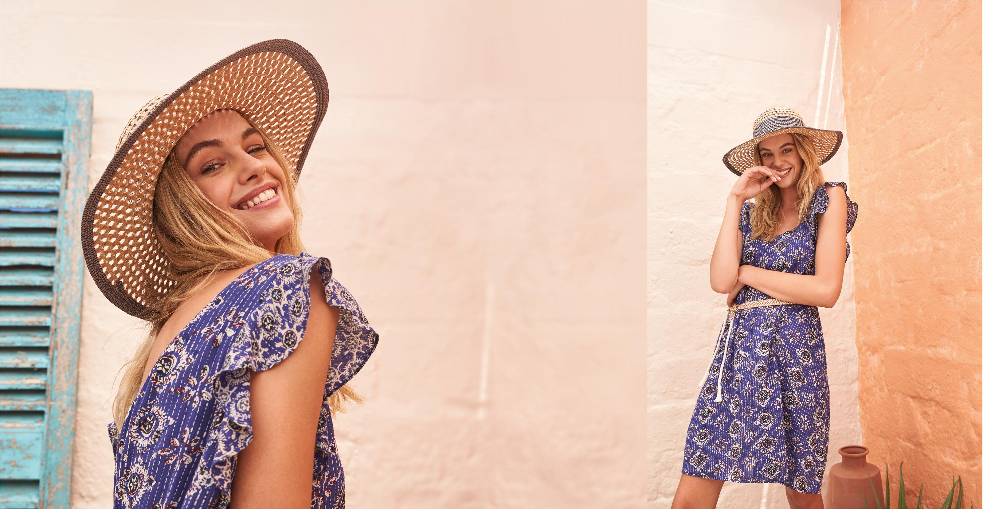 Image of female model wearing the Tori Tile Patch Geo Dress in Blue with summer straw bag.