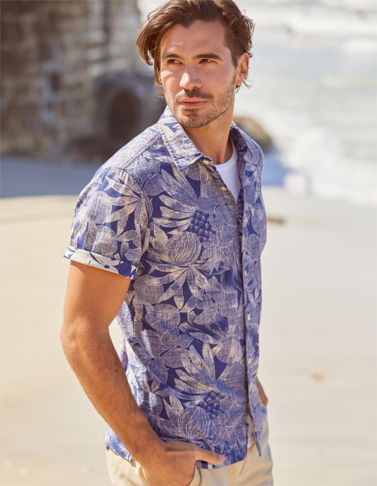 Image of male fatface model wearing a blue hawian printed shirt
