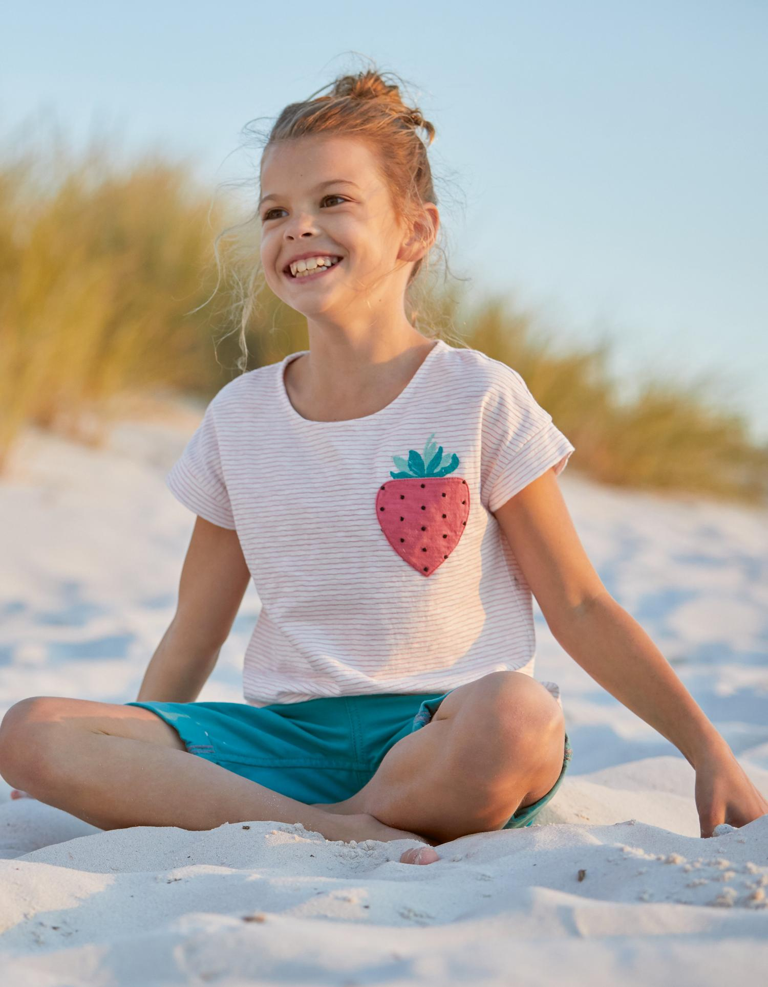 Fatface girl model wearing a light pink top with a strawberry print and turquoise shorts.