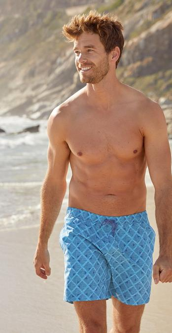Fatface male model in blue swim shorts on the beach.