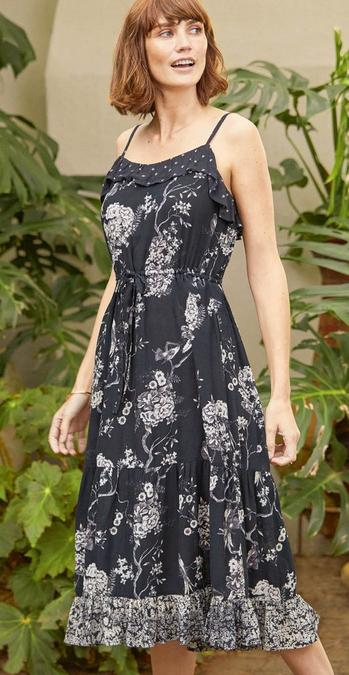 Fatface female model wearing a starppy dress in our oriental garden print, with big leaves in the background. The dress in a black base with white flowers, tie waist and frills at the top and bottom of the dress.