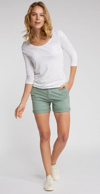 Fatface female model wearing long sleeve white top, and green shorts.