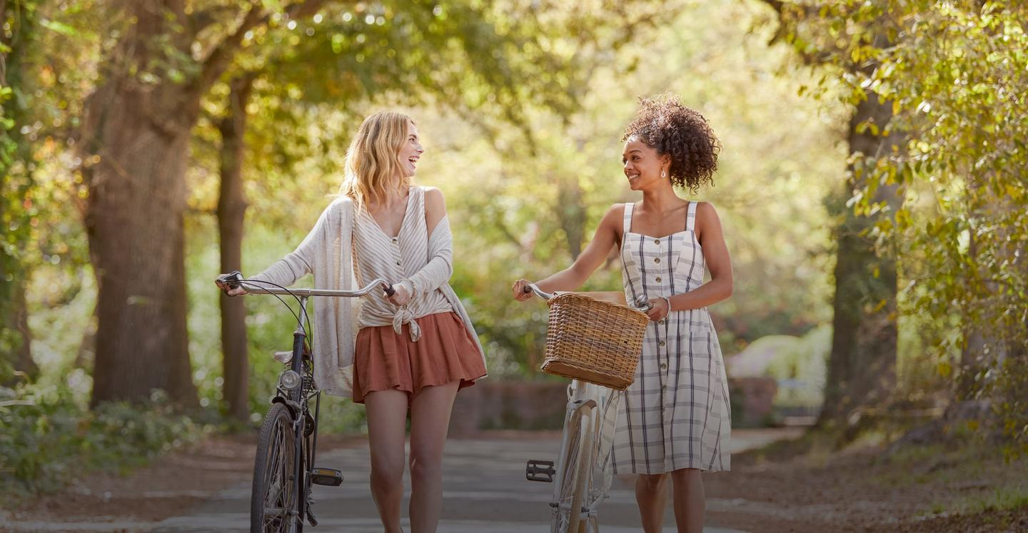 Two female FatFace models walking with bicycles in the park. Buy one get one 50% off on all women's dresses and knitwear.