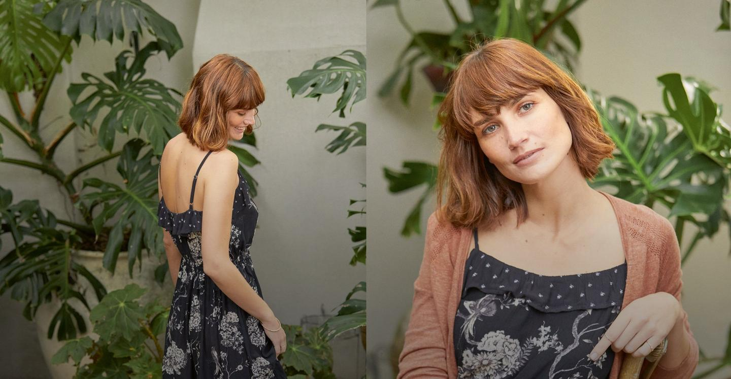Two images of a female Fatface model wearing our oriental garden dress in black and white print with a pink Rose cardigan.