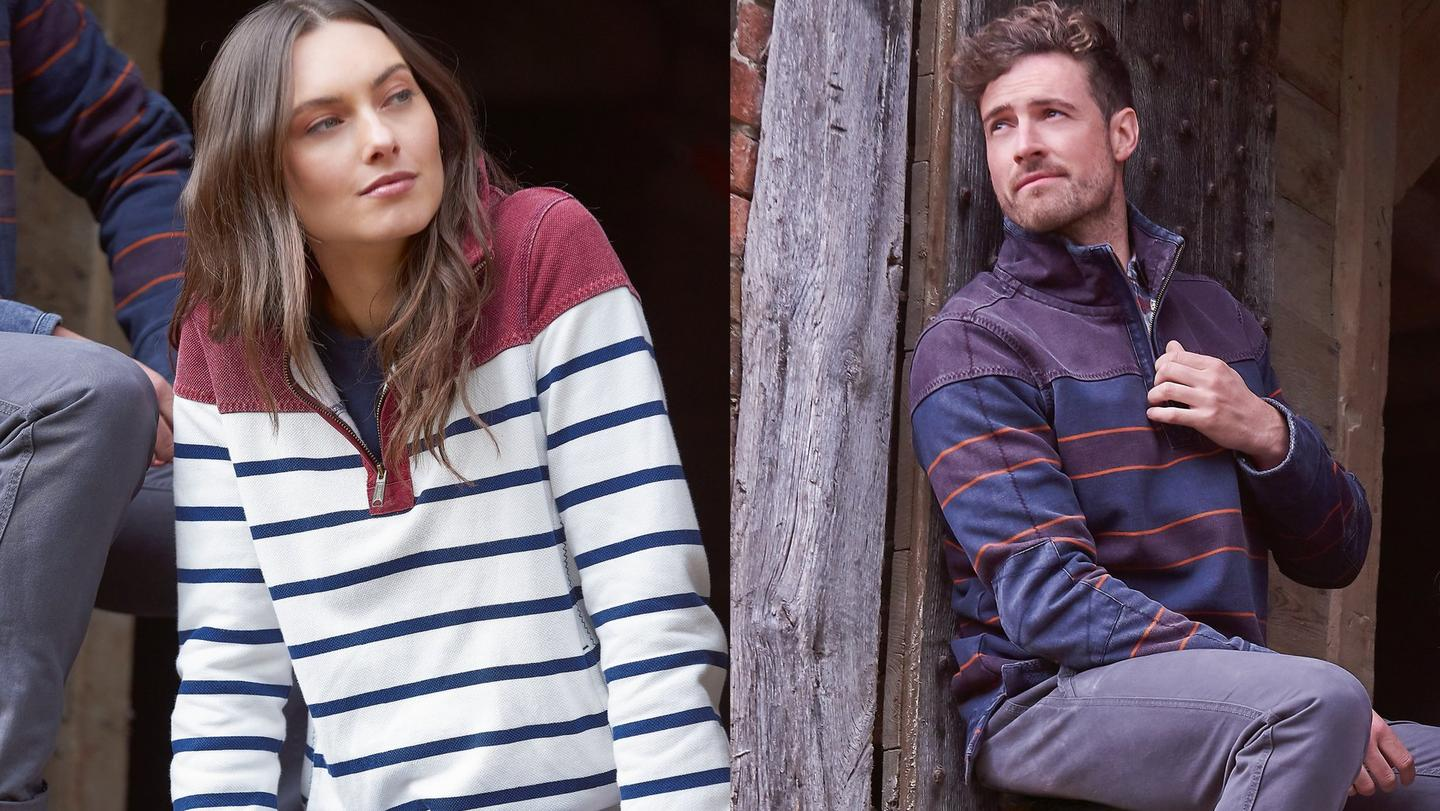 A man and a woman wearing striped Airlie Sweatshirts, sitting in a brick hole in a wall.