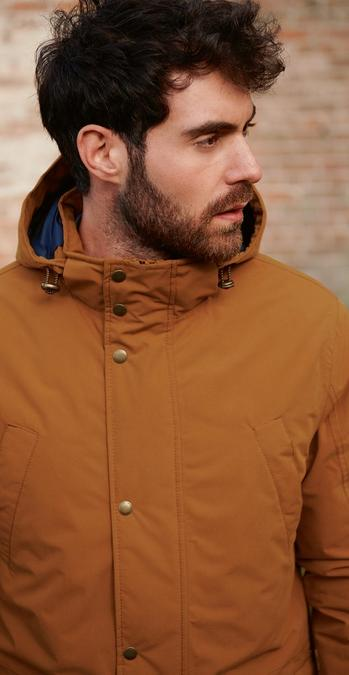Male model wearing a dark mustard colour parka made from recycled bottles.