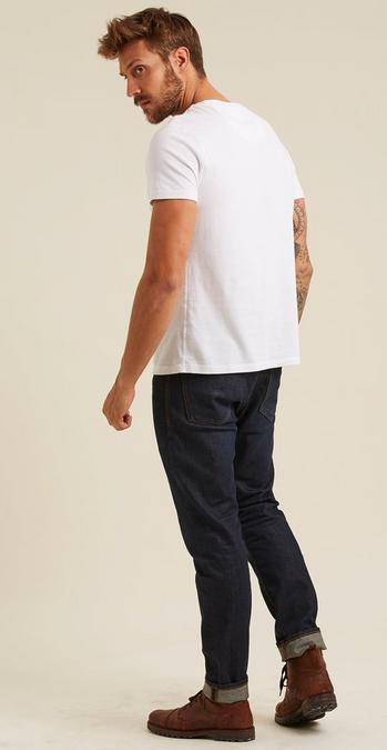 Male model with his back turned wearing a plain white tee and dark wash jeans.