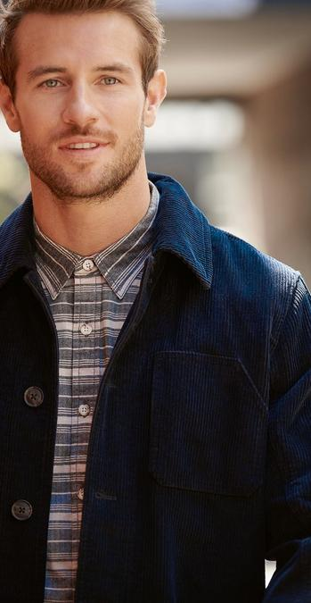 Male model wearing a navy thick cord worker shirt.