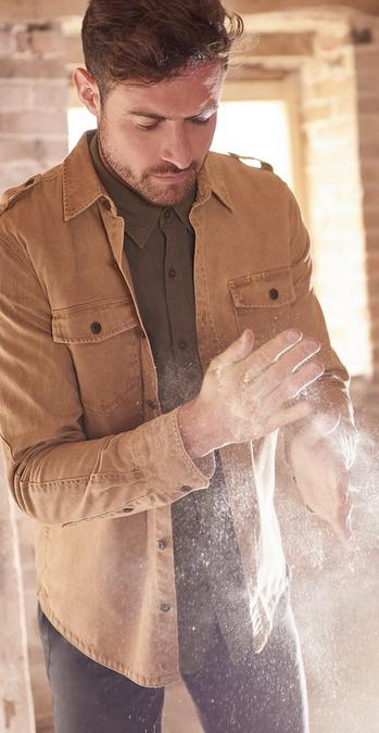Male model dusting off his hands wearing a stone utility shirt.