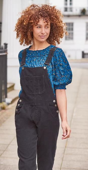 Female FatFace model wearing a blue abstract print statement blouse with shirred collar under blue cord dungarees.