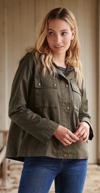 Female FatFace model wearing the khaki Rutland Utility Wax Jacket with blue jeans.