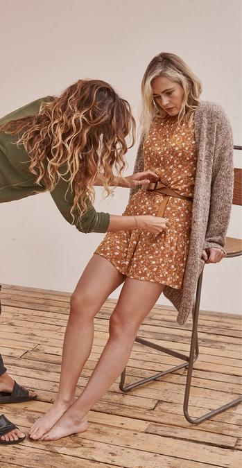 Female FatFace model leaning on a stool being styled by Angie Smith, wearing a mustard and white ditsy print Trellis Floral mini dress, layered with a long length cardigan.