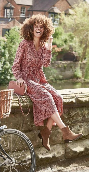 Female FatFace model sat on a wall beside a river in the UK, wearing a pink floral ditsy print midi dress and tan ankle boots.