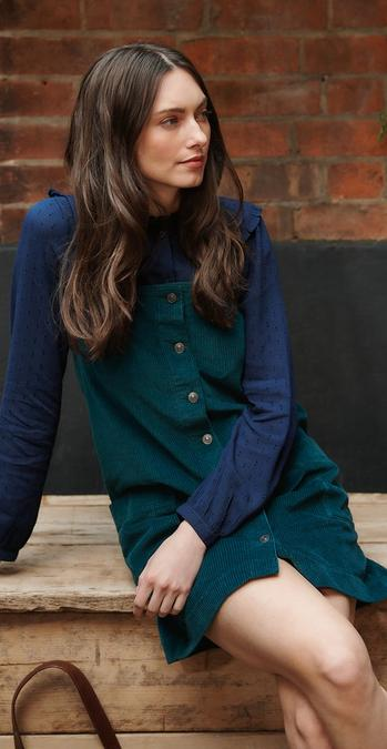 Female model wearing a bottle green Sabrina cord pinafore dress layered over a navy long sleeve blouse.