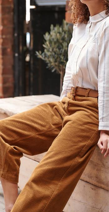 Female model wearing mustard corduroy wide leg crop trousers and an ivory long sleeve blouse.