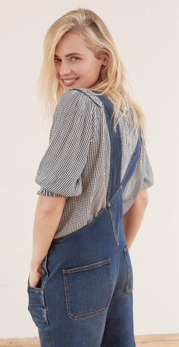 Female model wearing a navy gingham blouse underneath denim dark blue wash Lewes Dungarees.
