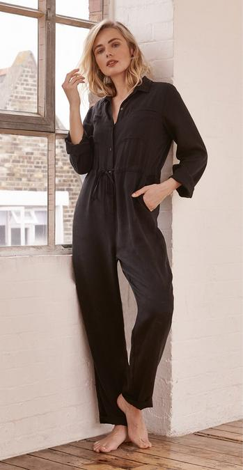 Blonde FatFace model wearing a the Jackie Shirt Jumpsuit, a black button up boiler suit with a drawstring waist, leaning against a window.