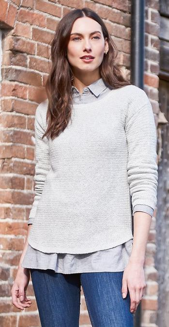 Brunette female FatFace model wearing a light grey Harpenden Jumper layered over a grey shirt and dark wash jeans.