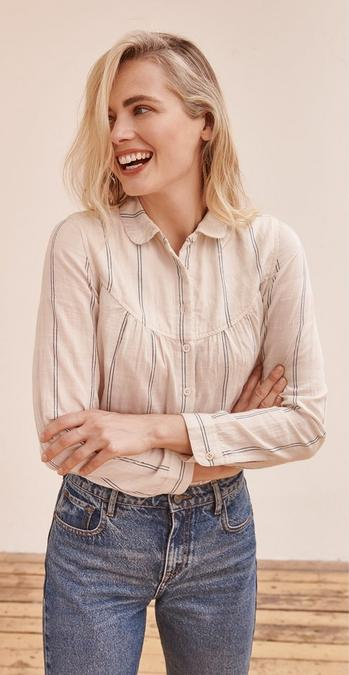 Blonde female FatFace model smiling wearing a ivory and blue Allyra Stripe Shirt tucked into vintage wash jeans.