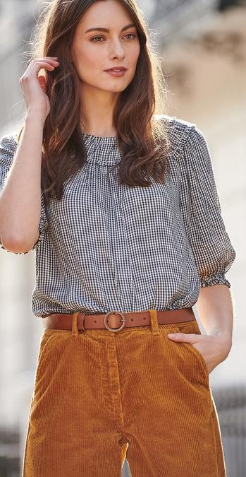 Female FatFace model wearing a navy gingham elizabeth blouse with a shirred collar with mustard cord wide leg crop jeans.