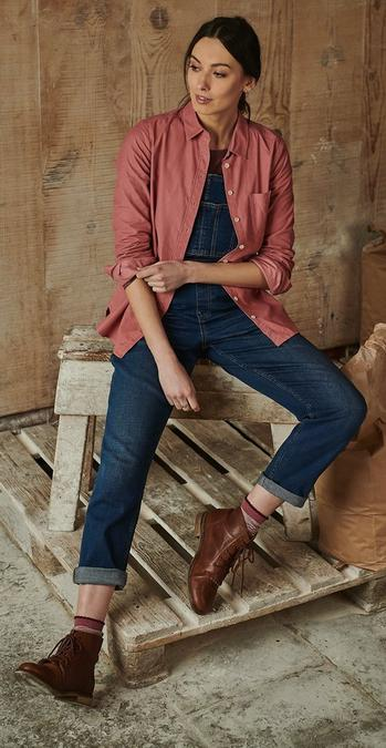 Female model sat on a work bench wearing a rose red Olivia plain shirt, over dark wash denim dungarees and dark brown lace up boots.