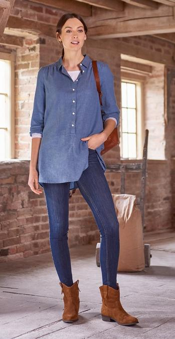 Female model stood in a empty barn wearing a chambray blue longline shirt, dark denim jeans and tan ankle boots.