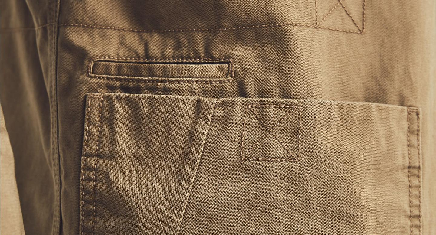Detail close up image of sand coloured cargo shorts.