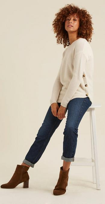 Female model wearing a long sleeved cream jumper with side button detailing, rolled up blue jeans and tan brown boots.