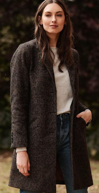 Female FatFace model wearing the bronze herringbone wool coat by Abraham Moon and Sons.