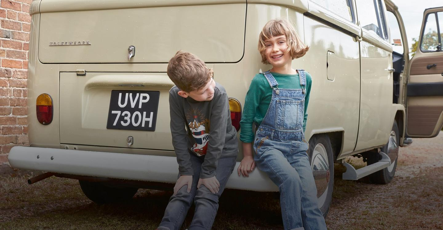 Boy wearing a grey graphic top with jeans and girl wearing a blue and green striped top and dungarees, leaning against a van.