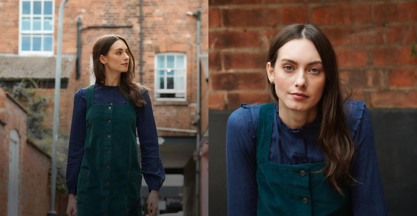 Female model wearing a navy blue blouse and a green cord pinafore dress.