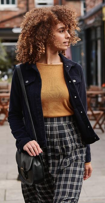 Female model wearing a navy blue cord jacket with a mustard jumper, check skirt and black bag.