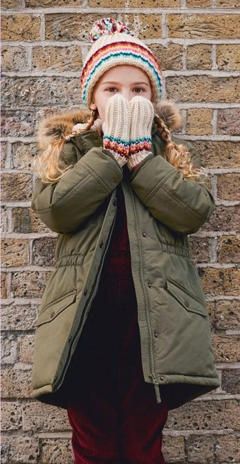 Fatface girl model wearing a khaki green coat with cream gloves and hat which have colourful stripe detail in red, blue, green and yellow.