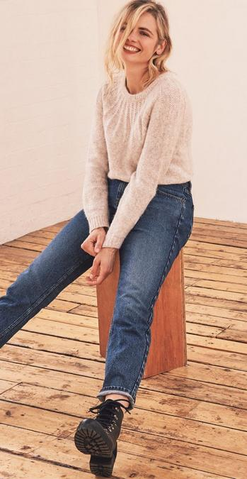 Fatface female model wearing a cream jumper and blue jeans.