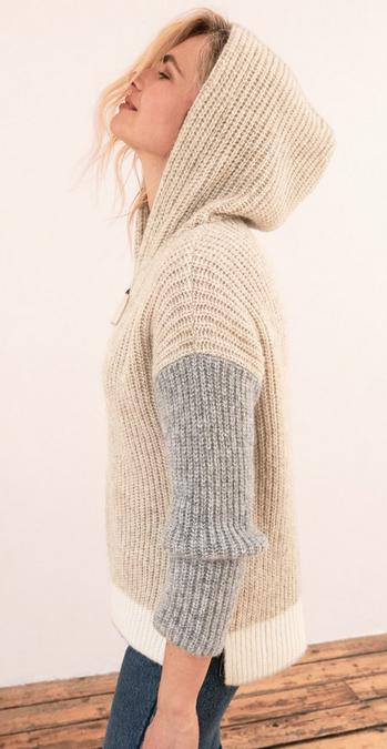 Fatface female model wearing a cream jumper with grey sleeves.