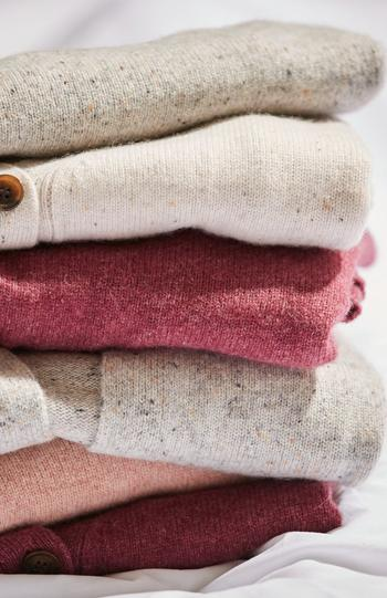 Fatface image of folded cashmere jumpers and cardigans in different shades of red, pink and cream.