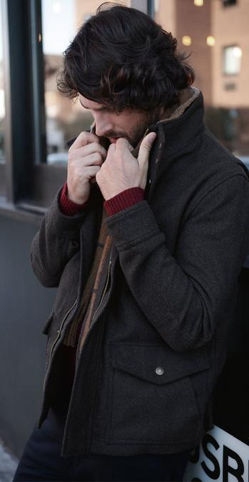 Fatface male model wearing a dark brown coat.