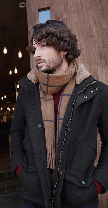 Fatface male model wearing an black coats and light brown scarf.