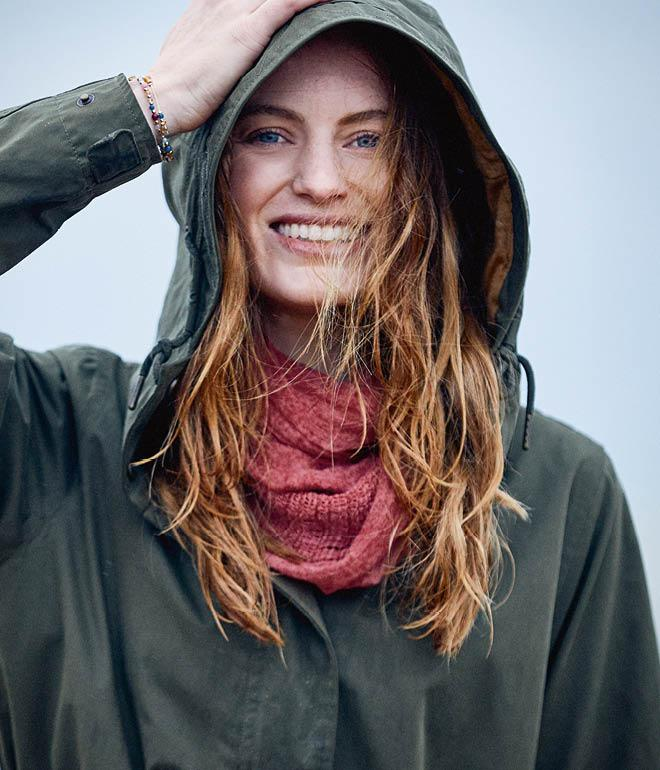 Shot of a female model wearing a green jacket as well as a red snood.