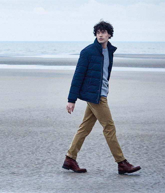 Shot of a male model wearing a navy blue puffer jacket with sand coloured chinos and brown boots.