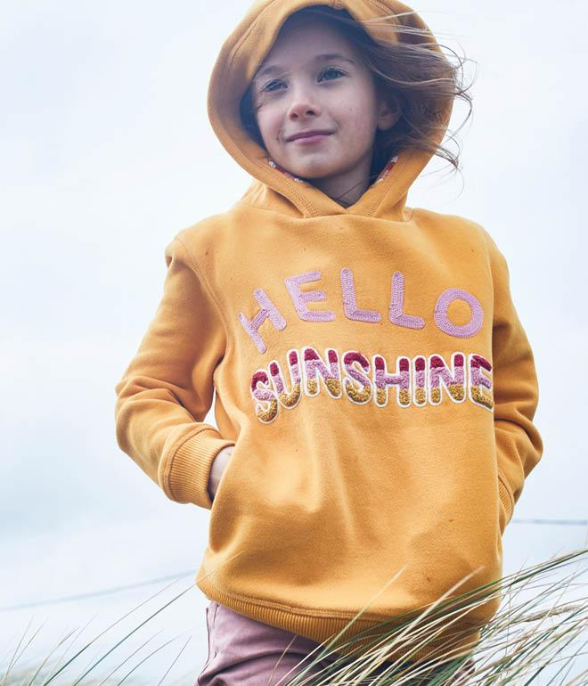 Image of a girl model wearing a yellow hooded sweatshirt with hello sunshine across the front.