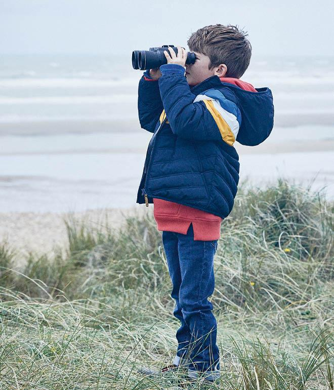 Image of a boy model wearing a blue, yellow and white chevron puffer jacket, red hoodie and jeans.