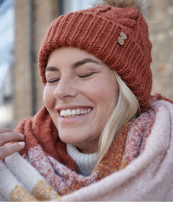 Female model wearing a scarf and wooly hat smiling