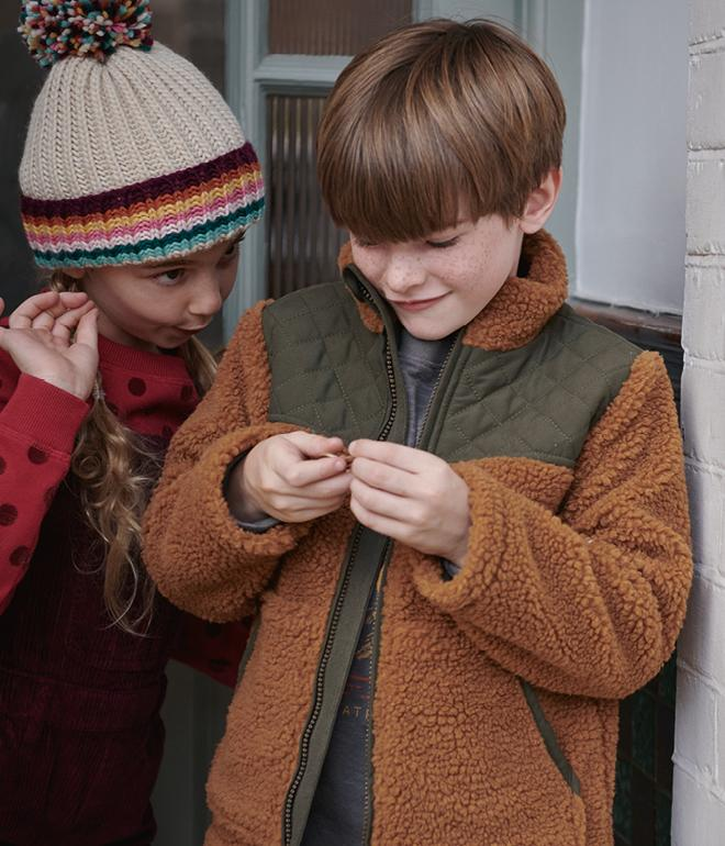 Boy wearing brown coat holding something in his hand, Girl wearing a wooly hat and coat looking at the boy