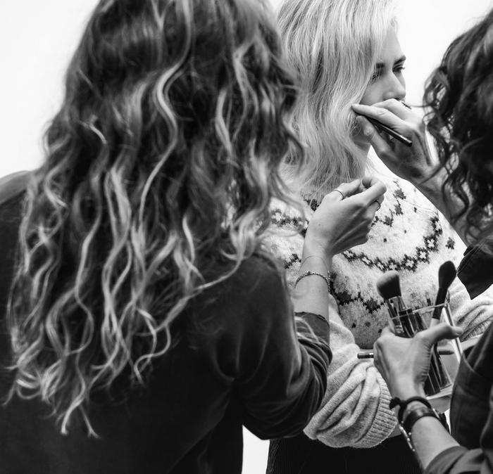 Black and white image of UK Stylist Angie Smith talking to other stylists, styling clothes on a model.