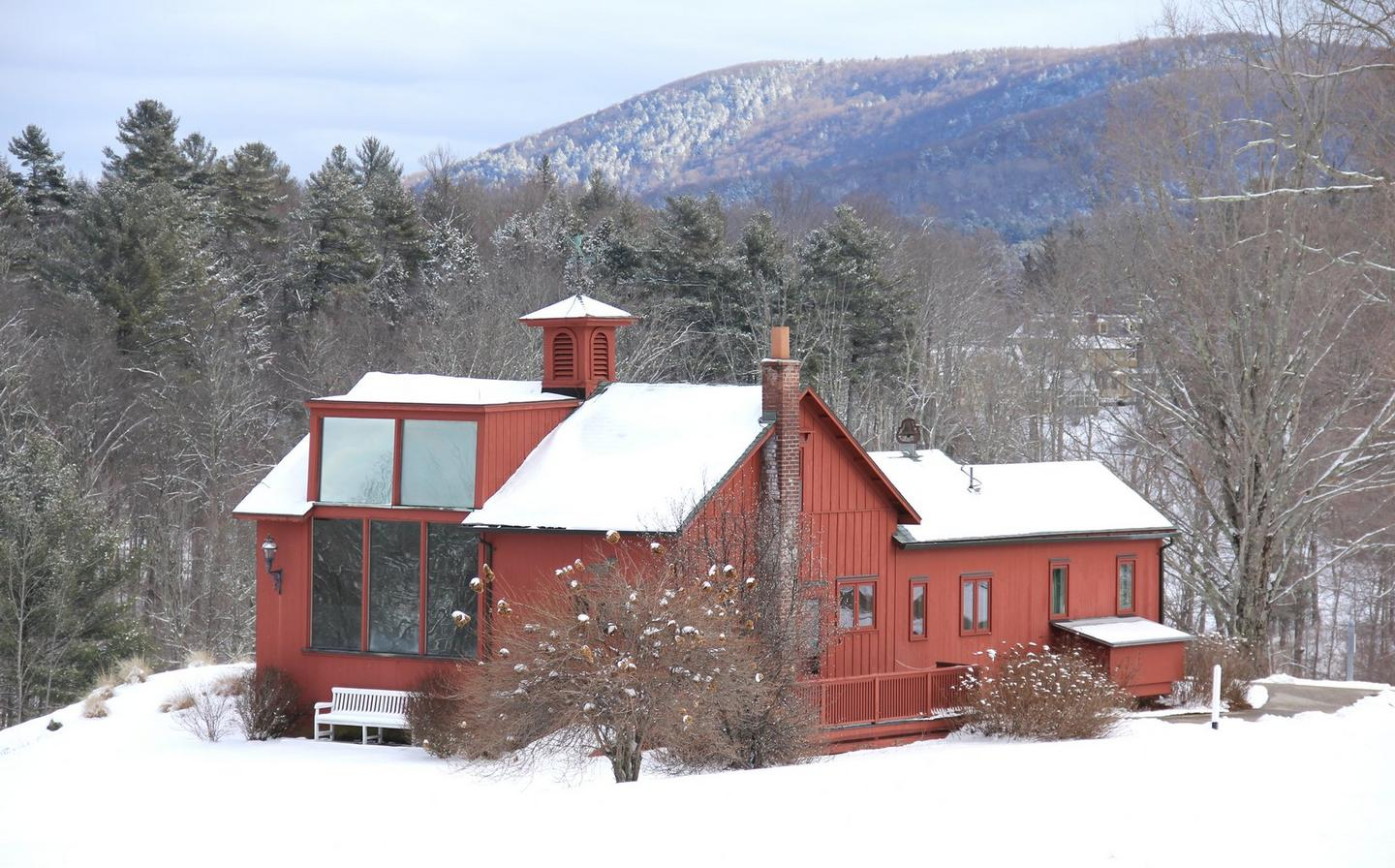 A large, red painted wooden cabin on a snowy hillside, surrounded by forest.