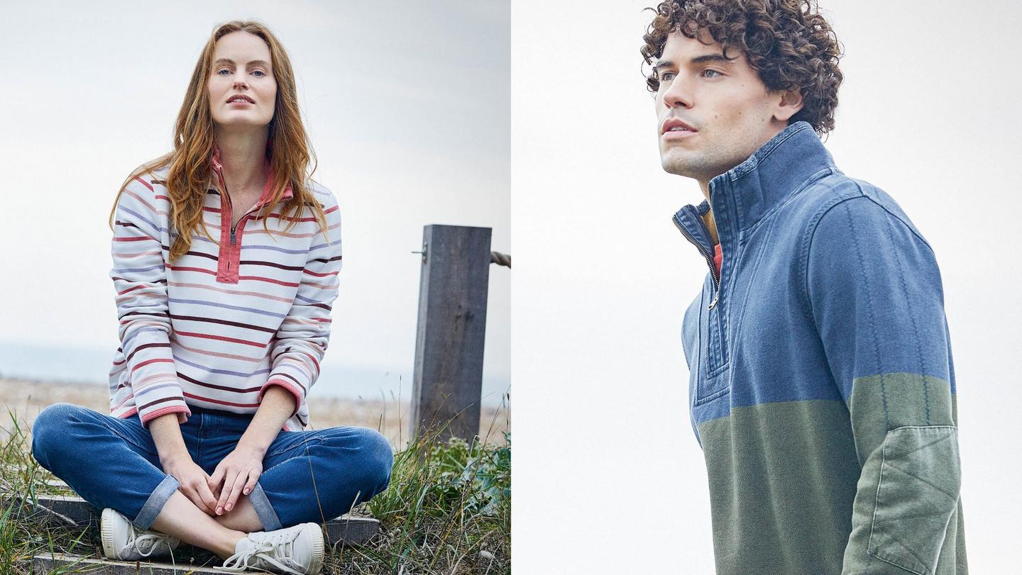 Female  model wearing a white and pink striped half neck Airlie sweatshirt and a male model wearing navy and green half neck Airlie Sweatshirt.