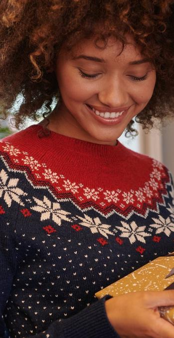 Female model wearing a navy and red fairisle jumper.